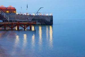 molo della marina di notte in arrivo raggi di sole foto