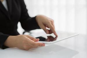 compressa bianca di tocco della mano della donna con lo schermo vuoto in bianco foto
