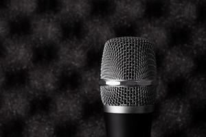 primo piano senza fili del microfono su fondo acustico della schiuma