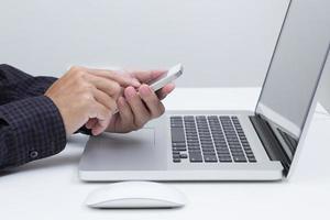 mani dell'uomo che tiene smart phone con sfondo di computer portatile foto
