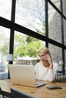 donna d'affari parlare su smartphone mentre si guarda allo schermo net-book foto
