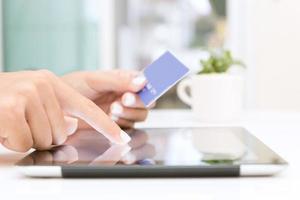 mano del primo piano facendo uso della compressa e della carta di credito che comperano online foto
