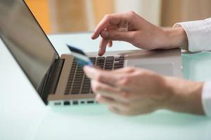 un uomo che usa la sua carta di debito per acquistare oggetti online
