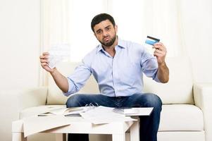 uomo d'affari latino bello preoccupato pagare le bollette sul divano foto
