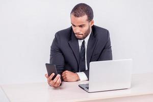 chiamata del cliente. uomo d'affari africano sorridente che si siede ad uno scrittorio e foto