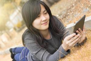 Le donne usano tablet nel parco, Thailandia Bangkok foto