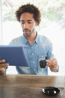 uomo casuale che mangia caffè mentre per mezzo della compressa foto