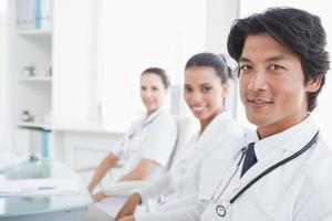 medici sorridenti seduti uno accanto all'altro foto