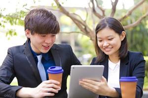 giovane dirigente aziendale asiatico maschio e femmina facendo uso della compressa foto