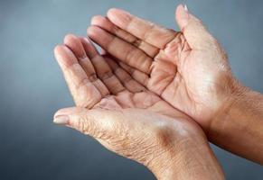 mani aperte della persona matura di fronte a sfondo grigio
