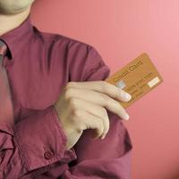 vista ritagliata della carta di credito della holding della mano dell'uomo d'affari foto