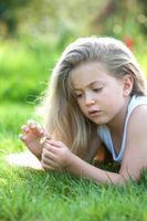 ragazza che mangia le fragole sull'erba foto
