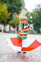 ragazzino felice con ombrello giallo e giacca colorata outdoo foto