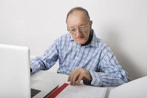 uomo d'affari maggiore che per mezzo del computer portatile mentre leggendo archivio alla scrivania foto