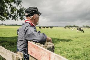 contadino anziano che guarda un gregge in un pascolo foto