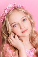 ragazza sveglia del bambino che propone sopra il colore rosa foto
