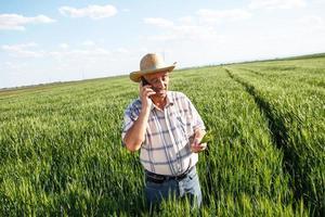contadino in piedi in un campo di grano e parlando al telefono foto