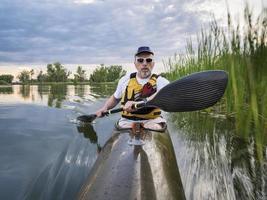 Pagaiando kayak di mare su un lago foto