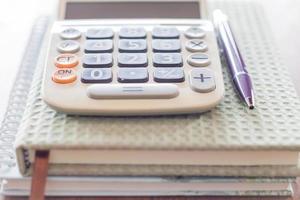 calcolatrice, penna e quaderni del primo piano foto