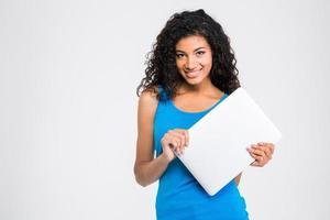computer portatile afroamericano sorridente della tenuta della donna foto