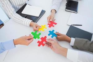 colleghi di lavoro in possesso di un pezzo di puzzle foto