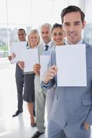 squadra di affari in una riga che tiene le pagine bianche foto