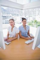 le donne di affari felici che lavorano si appoggiavano l'una contro l'altra foto