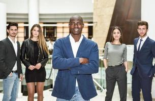 allegro giovane africano in abbigliamento formale tenendo le braccia incrociate foto