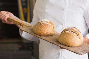 fornaio mostrando vassoio di pane fresco foto