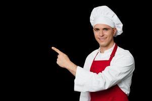 giovane chef che punta verso qualcosa foto