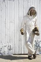 apicoltore in piedi davanti a una porta della stalla bianca foto