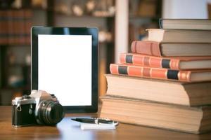 pila di vecchi libri e tablet sul tavolo di legno