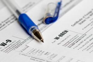 moduli di dichiarazione dei redditi con penna blu aperta foto