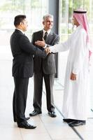 traduttore che presenta uomo d'affari musulmano al socio in affari foto