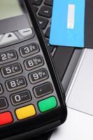 terminale di pagamento e carta di credito sulla tastiera del computer portatile, concetto di finanza foto