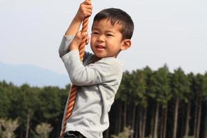 ragazzo giapponese che gioca con la corda tarzan foto