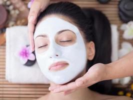donna che ha maschera facciale al salone di bellezza foto