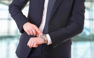 uomo d'affari che punta al suo orologio da polso. foto