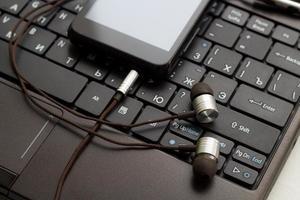 cuffie e telefono cellulare alla tastiera.
