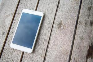 Smart Phone bianco sul tavolo di legno foto