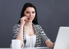 bella donna d'affari, lavorando alla sua scrivania con l'auricolare e