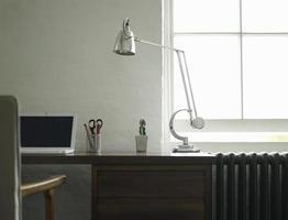 scrivania con computer portatile e lampada foto