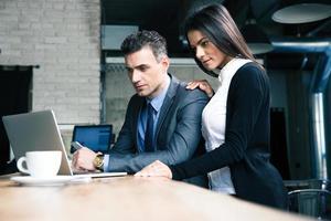 uomo d'affari e imprenditrice utilizzando il computer portatile nella caffetteria foto