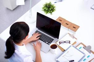 Ritratto di una donna d'affari seduto alla scrivania con il portatile foto