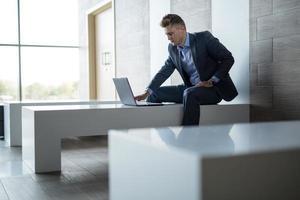 uomo d'affari seduto da solo su una panchina con il portatile foto