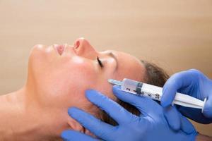 siringa mesoterapia viso antietà sul viso di donna foto
