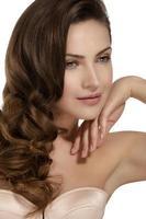 bellissima modella mostrando sani capelli castani ondulati foto
