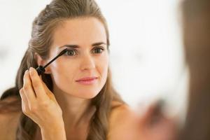 giovane donna che applica mascara in bagno foto