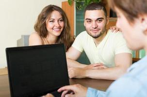 coppia felice a parlare con un dipendente foto
