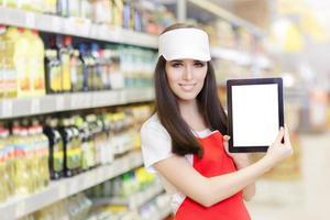 impiegato sorridente del supermercato che tiene un ridurre in pani del pc foto